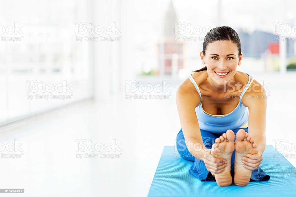 Woman Practicing Yoga In Health Club stock photo