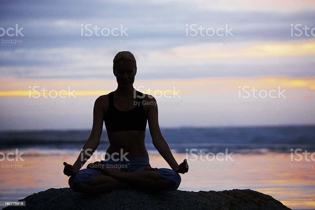Woman practicing yoga in lotus position royalty-free stock photo