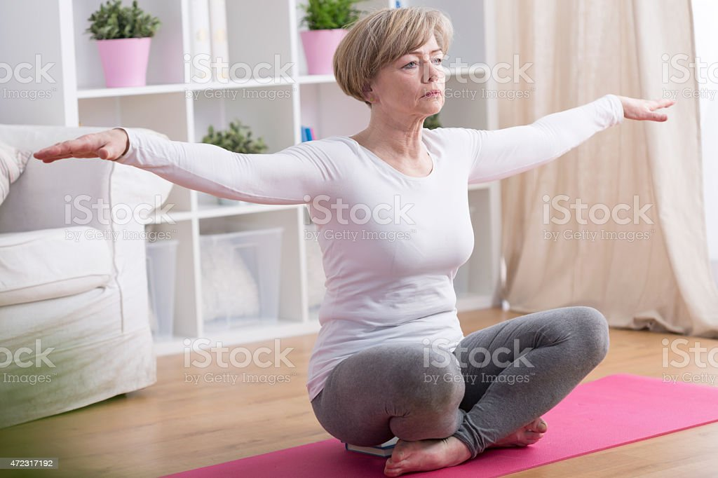 Woman practicing yoga in the comfort of her own home stock photo