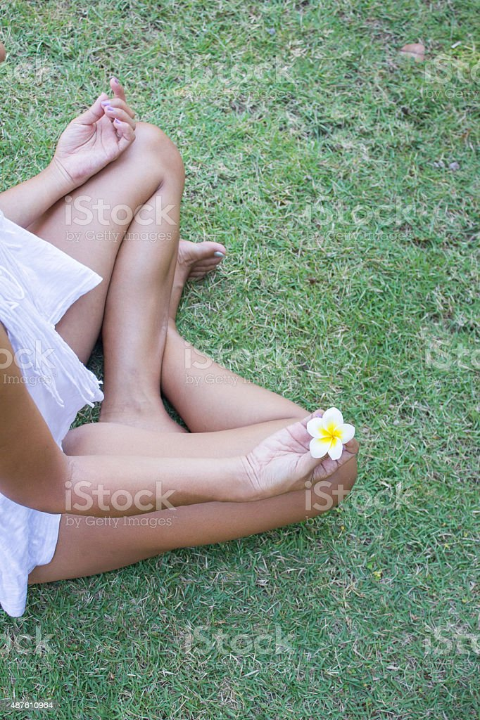 Woman practicing yoga in the green grass stock photo