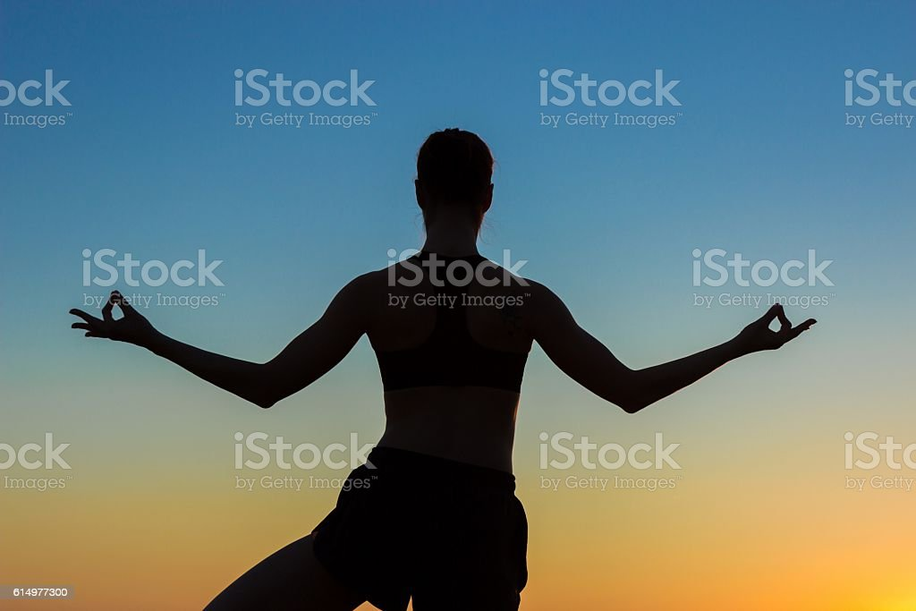 Woman practicing yoga in the park at sunset stock photo