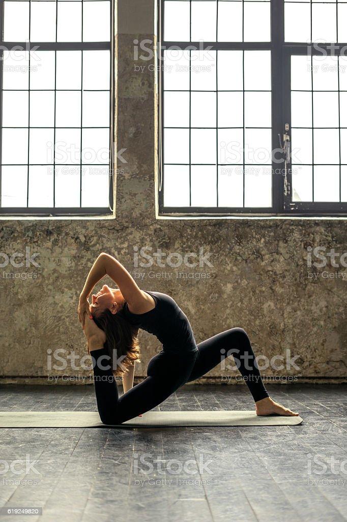 Woman practicing yoga in urban loft: King Pigeon Pose II stock photo