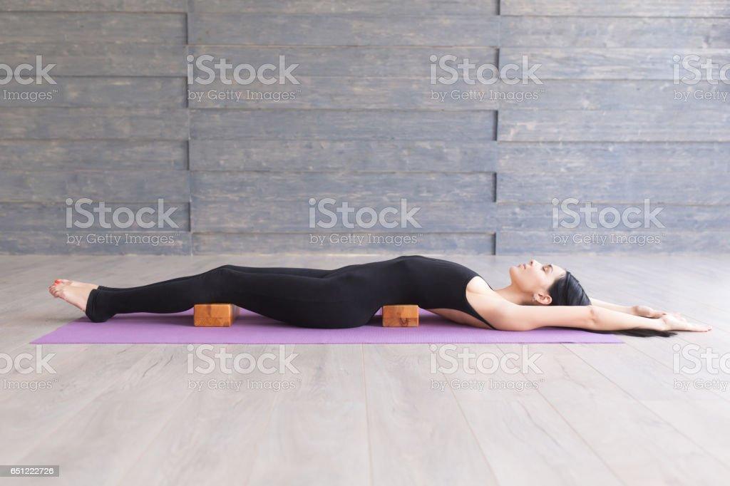 Young woman practicing yoga indoors on studio. Relaxing, meditating...