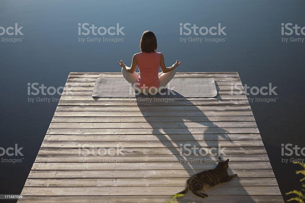 Woman Practicing Yoga Lotus Pose royalty-free stock photo