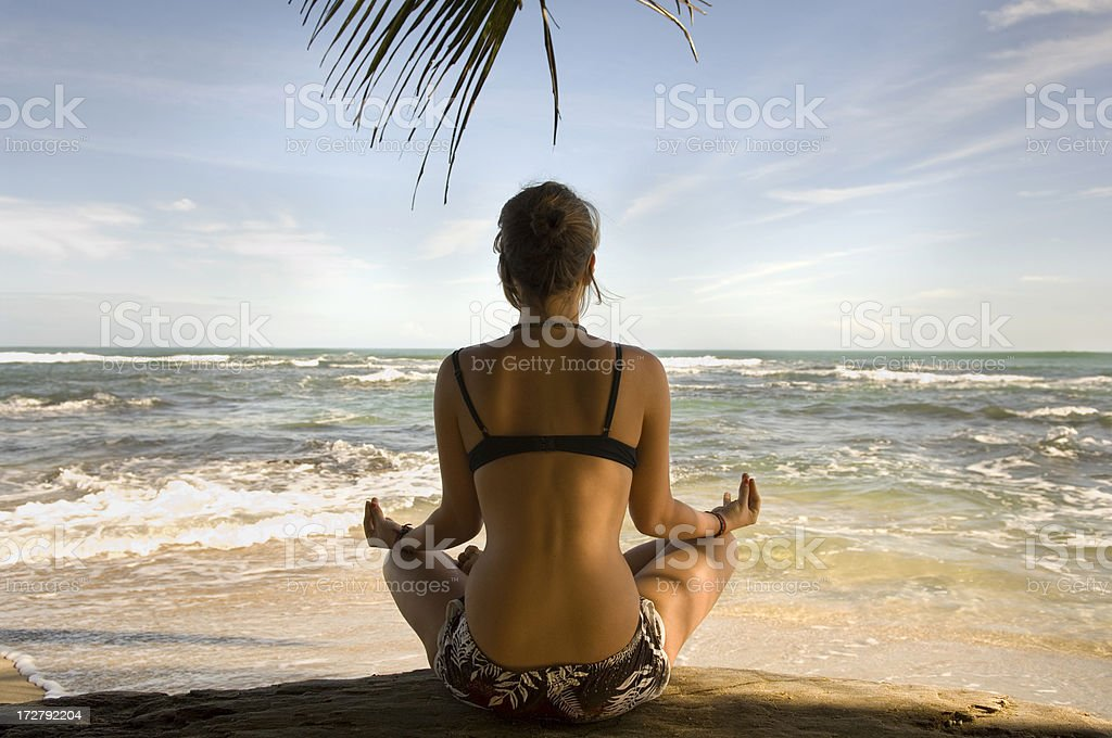 Woman practicing Yoga on beach in the lotus position royalty-free stock photo