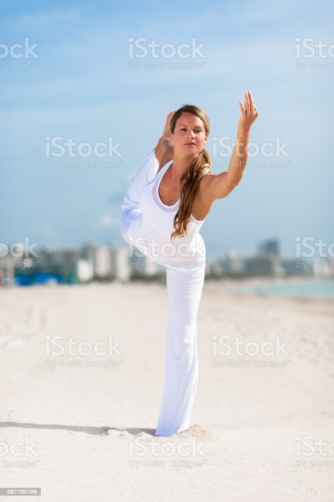 Woman Practicing Yoga on beach stock photo