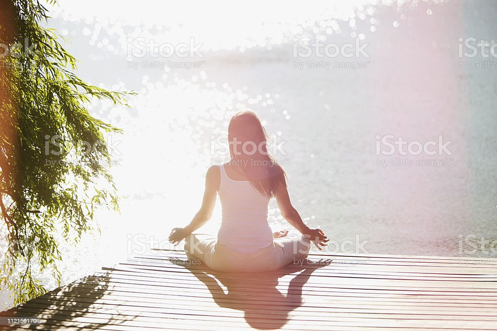 Woman practicing yoga on pier stock photo