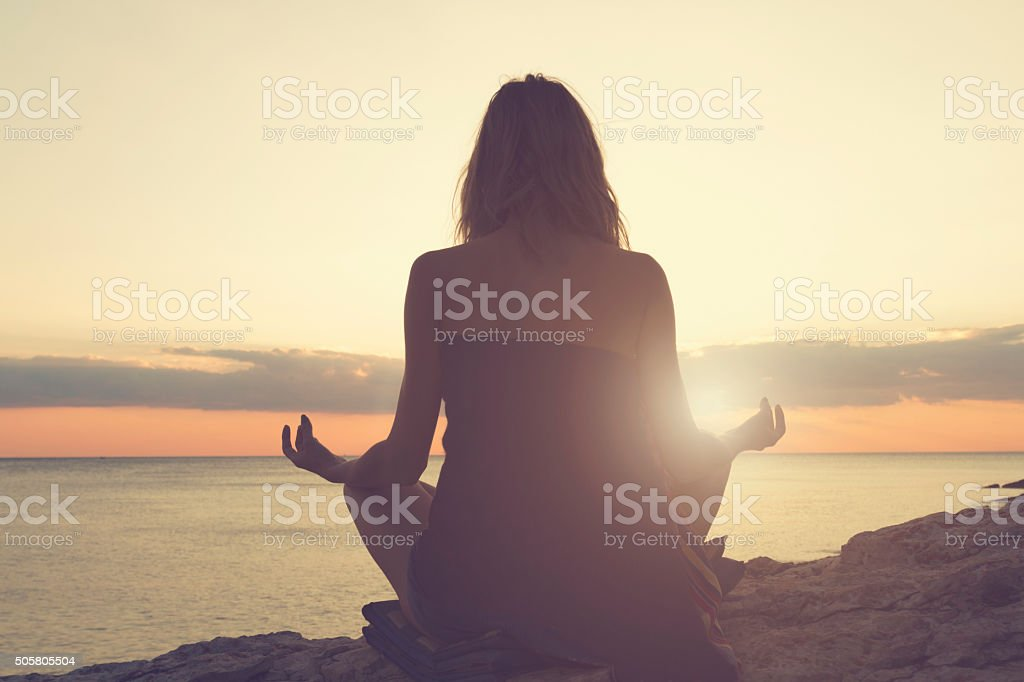 Woman practicing yoga on the beach. stock photo