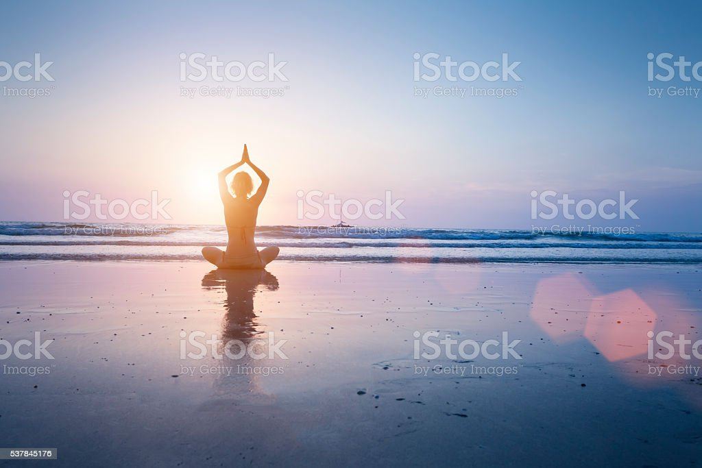 Woman practicing yoga on the beach stock photo