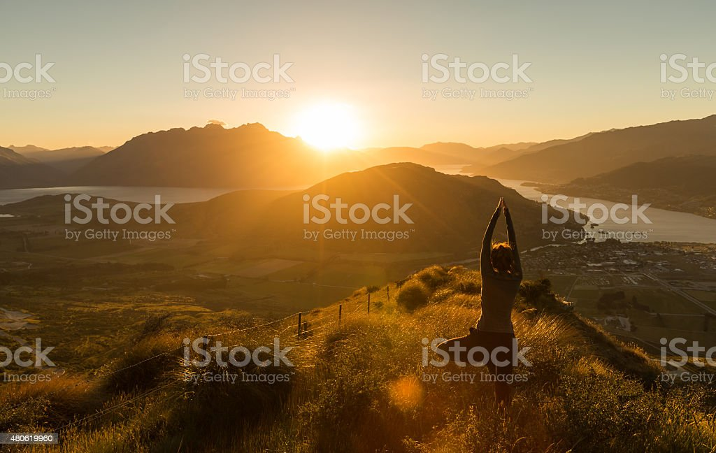 Woman practicing yoga silhouette at sunset on the mountain stock photo