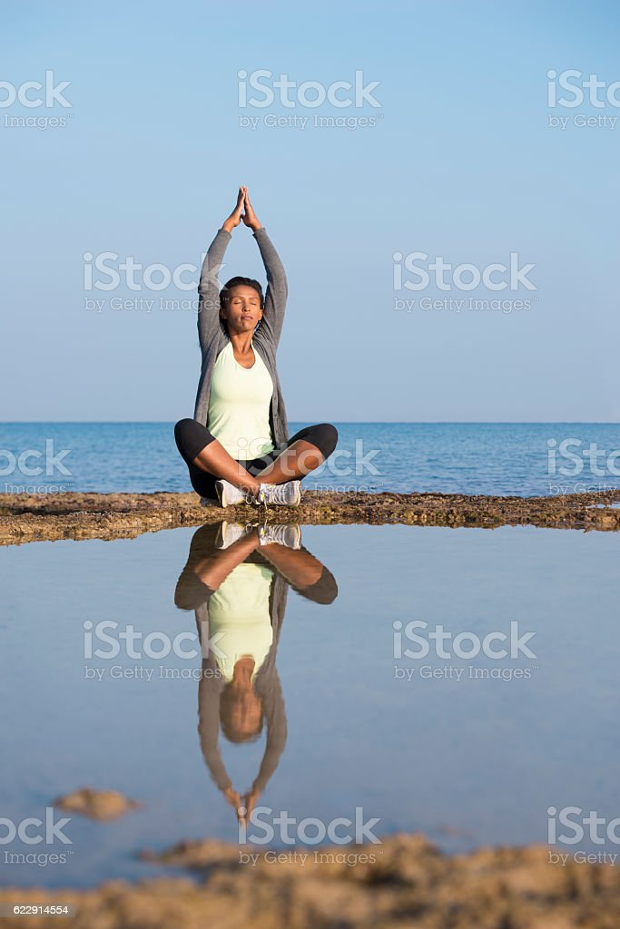 Woman practicing yoga sitting in lotus position on sea shore. stock photo