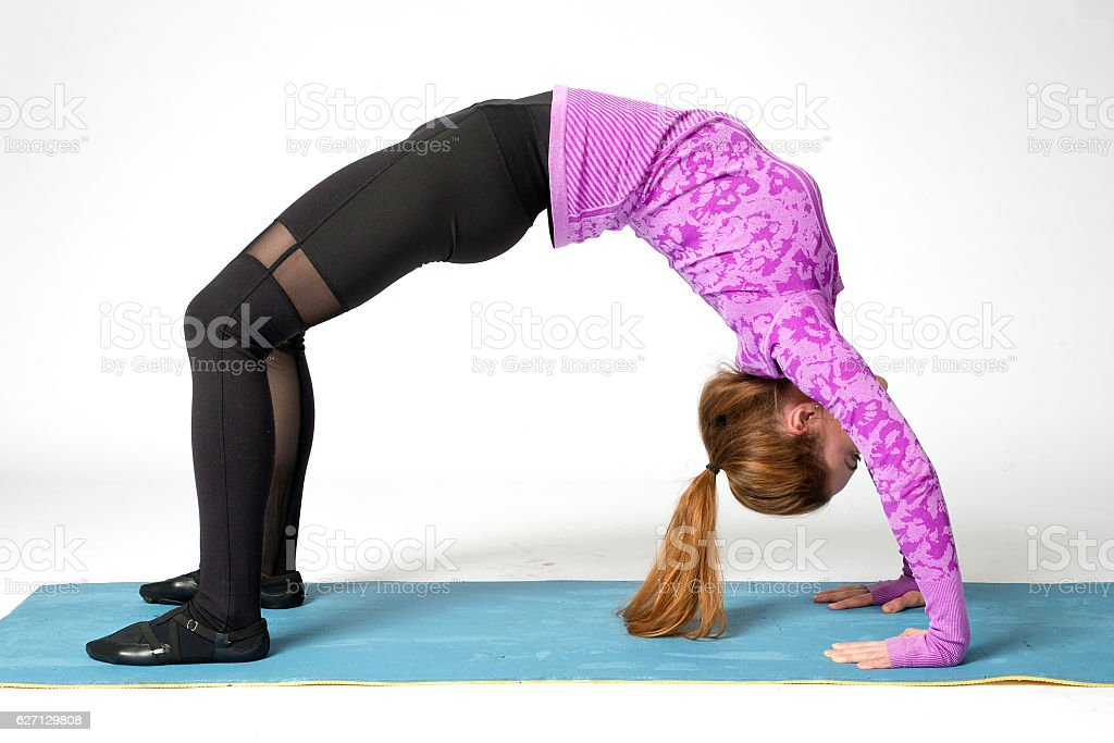Woman practicing yoga.Yoga-Urdhva Dhanurasana / Upward bow pose stock photo