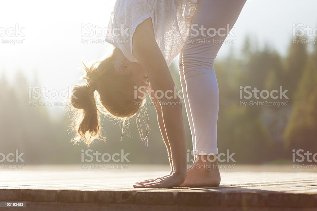 Woman practising yoga by the lake. stock photo