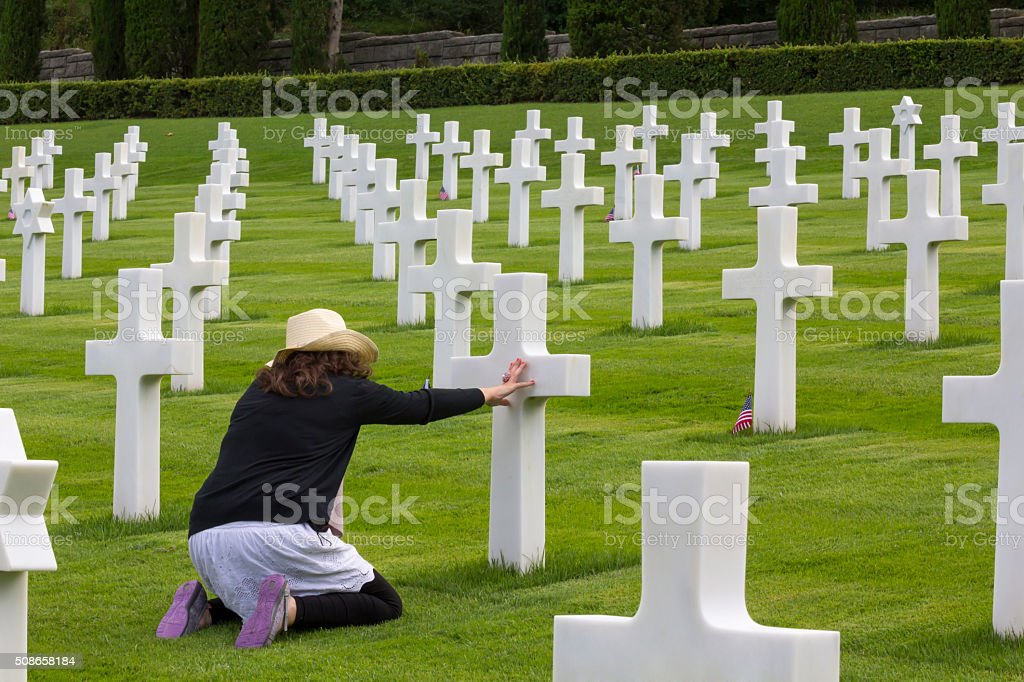 Woman praying in a memorial cemetery stock photo