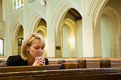 Woman praying in pews in church