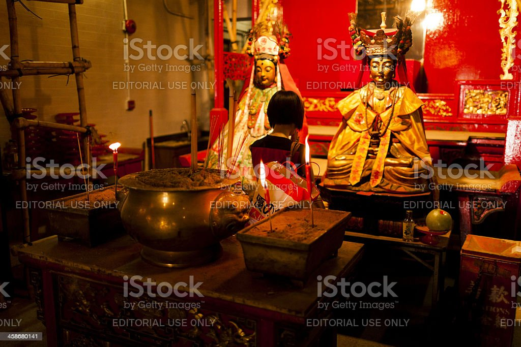 Woman praying in taoist temple of Man Mo royalty-free stock photo