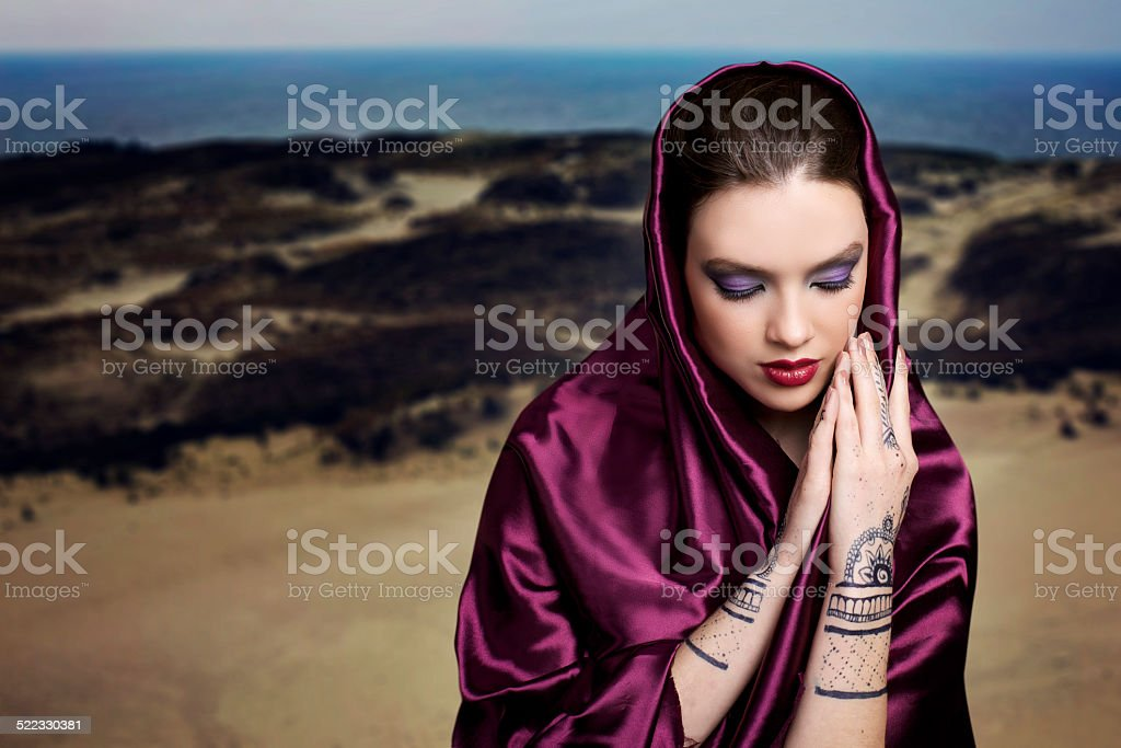 Woman praying in the desert with mehendi stock photo