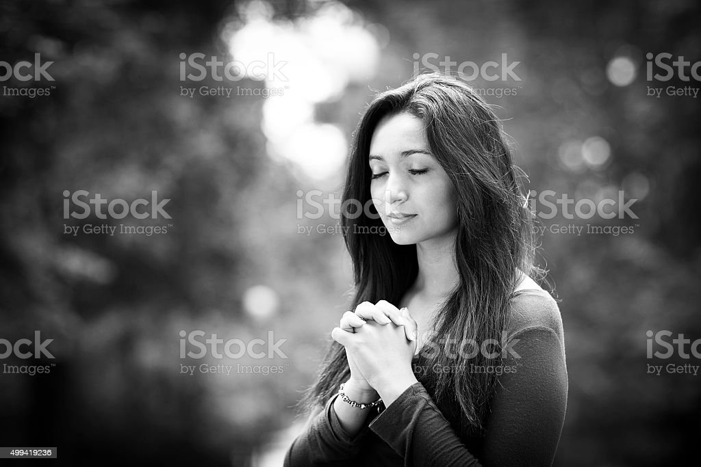 Woman praying outdoors stock photo
