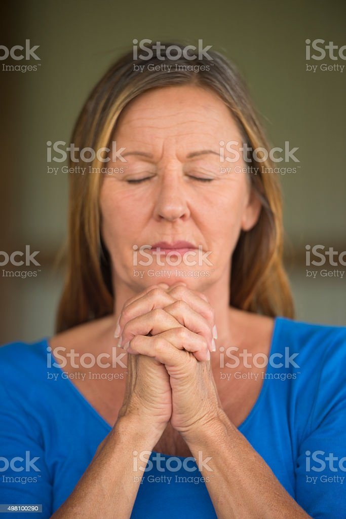Woman praying with closed eyes concentrated stock photo