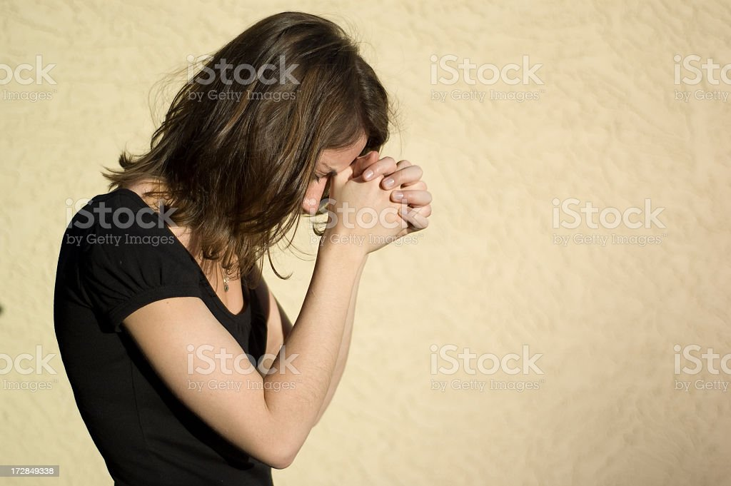 Woman praying with head slightly bowed royalty-free stock photo