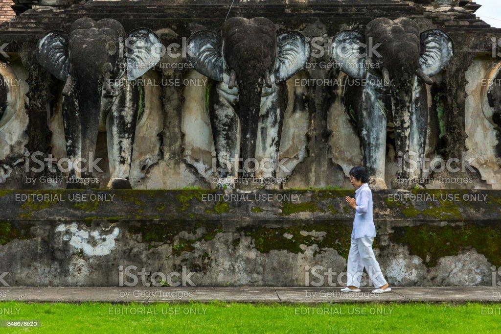 A woman prays at Wat Chiang Man temple in Chiang Mai, Thailand stock photo
