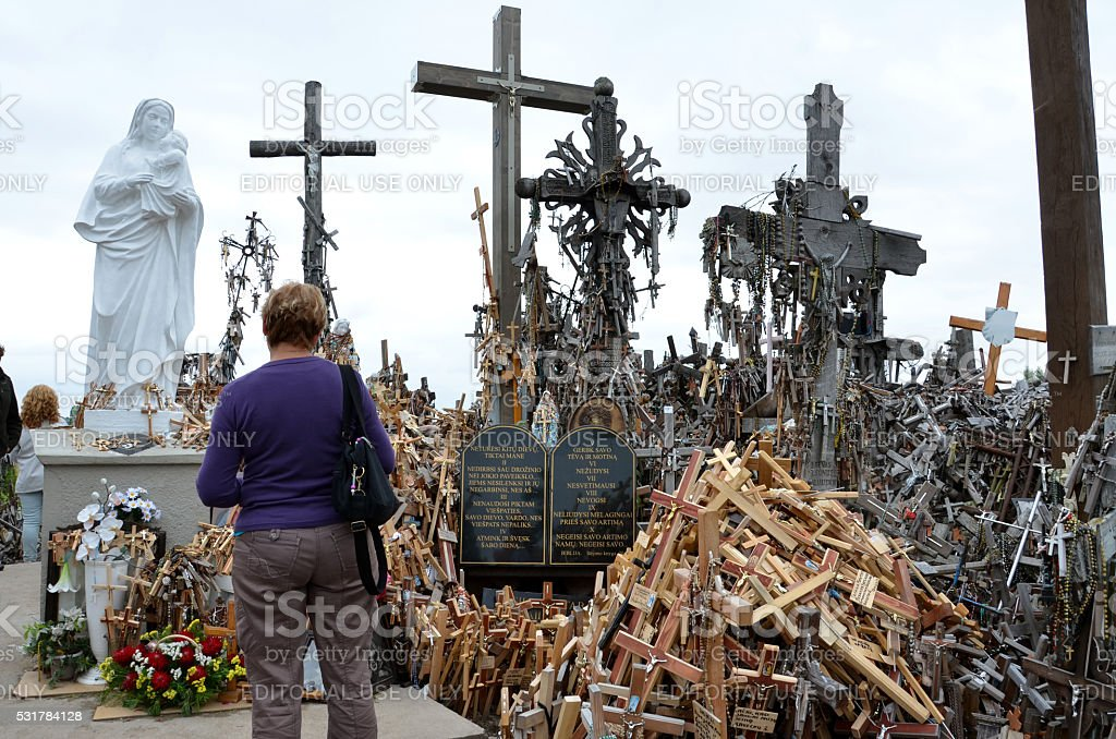 Woman prays on the Hill of Crosses in Lithuania stock photo