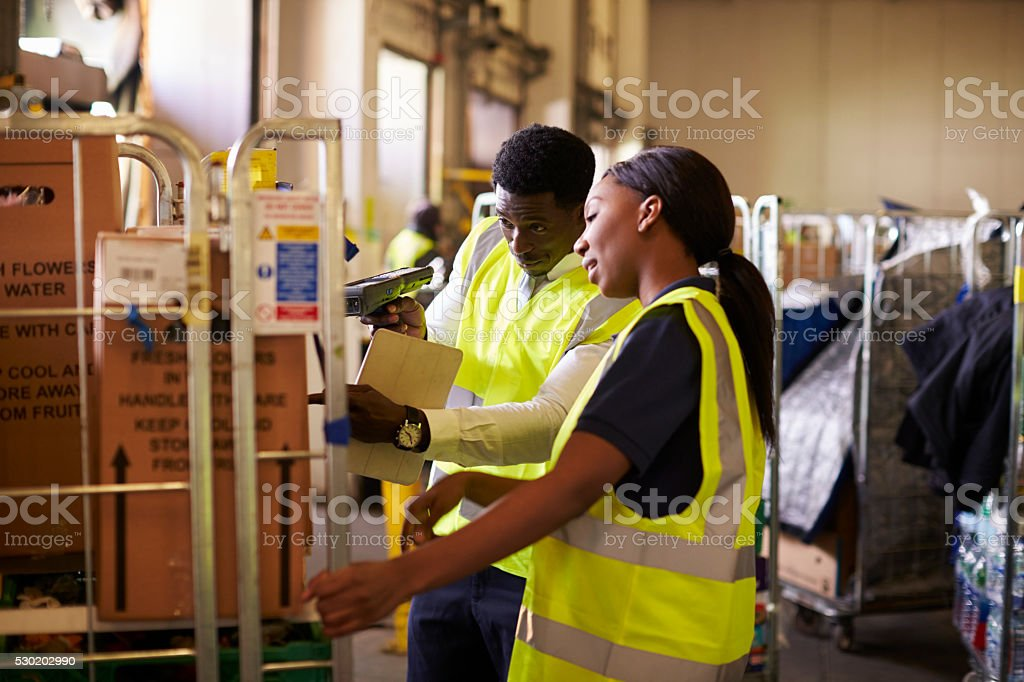 Woman prepares roll cage for delivery, checked by supervisor stock photo