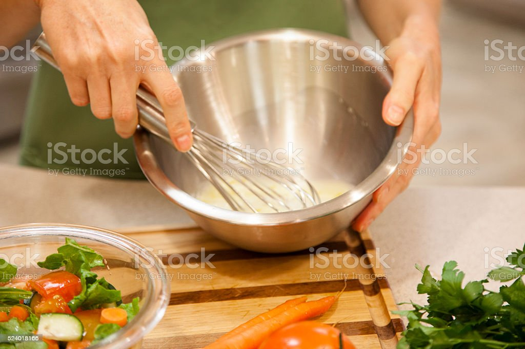 Woman prepares vegetable salad dressing in home kitchen. stock photo
