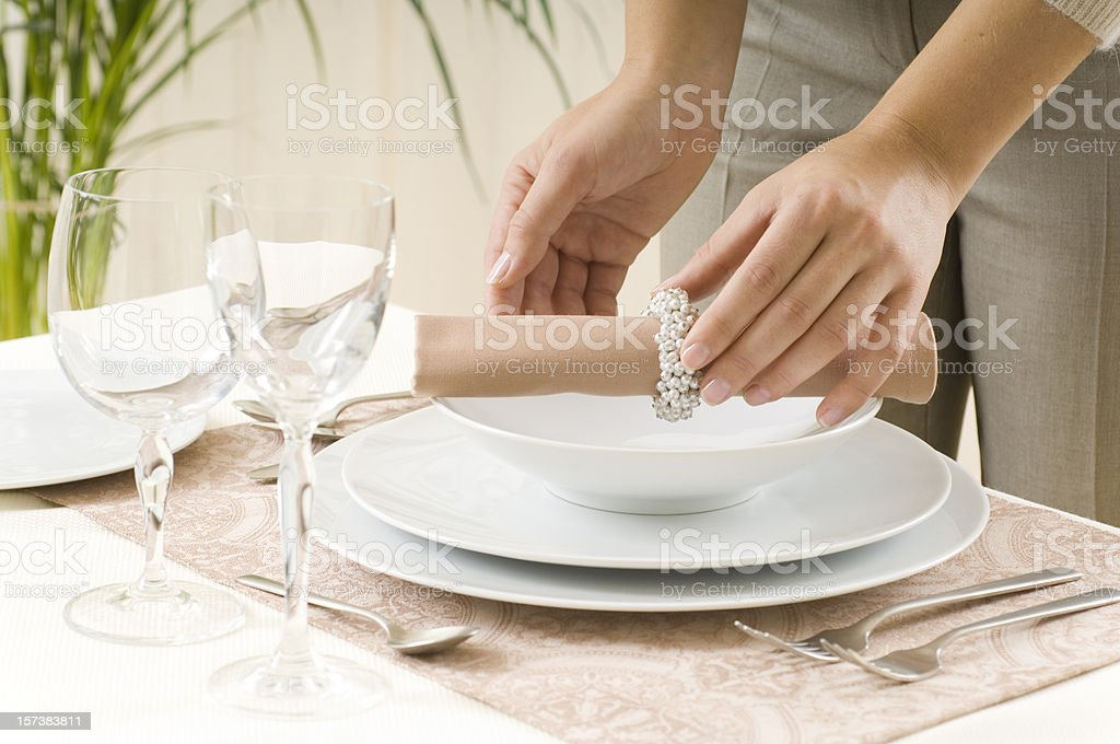 Woman preparing a dinner table stock photo
