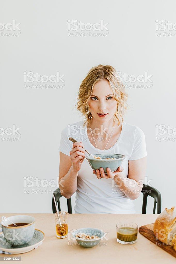 Woman preparing breakfast yogurt and cereals stock photo