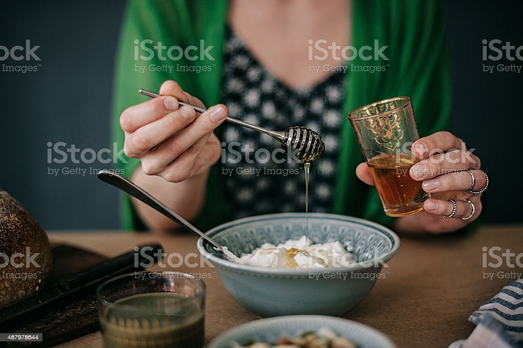 Woman preparing breakfast yogurt and honey stock photo