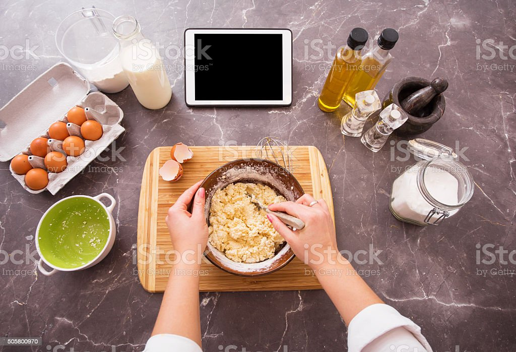 Woman preparing dough from recipe on her tablet stock photo