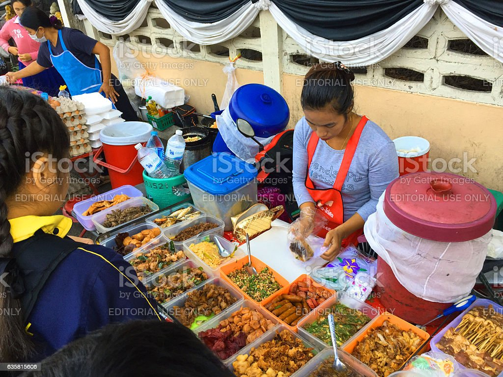 Woman preparing food for students in breakfast market stock photo