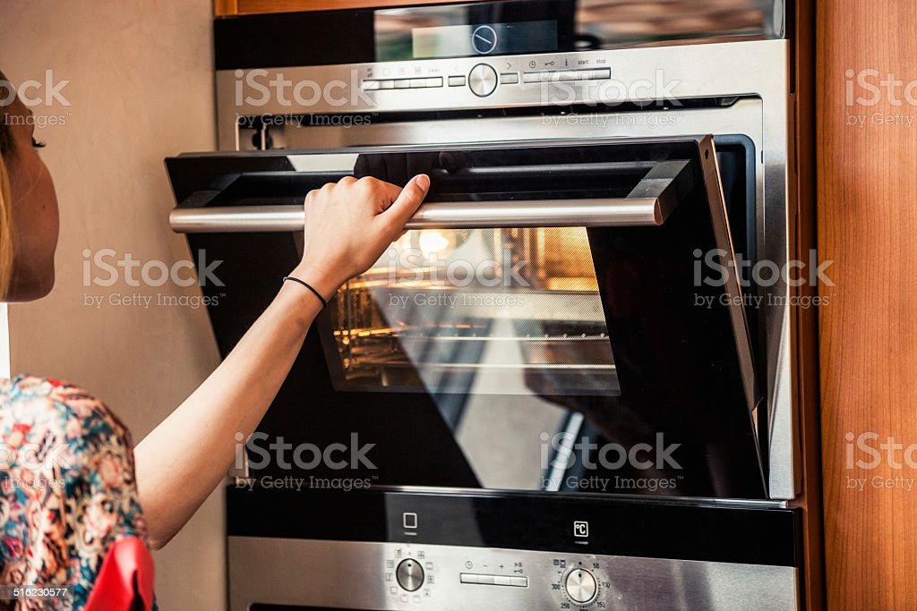 Woman preparing food on stove stock photo