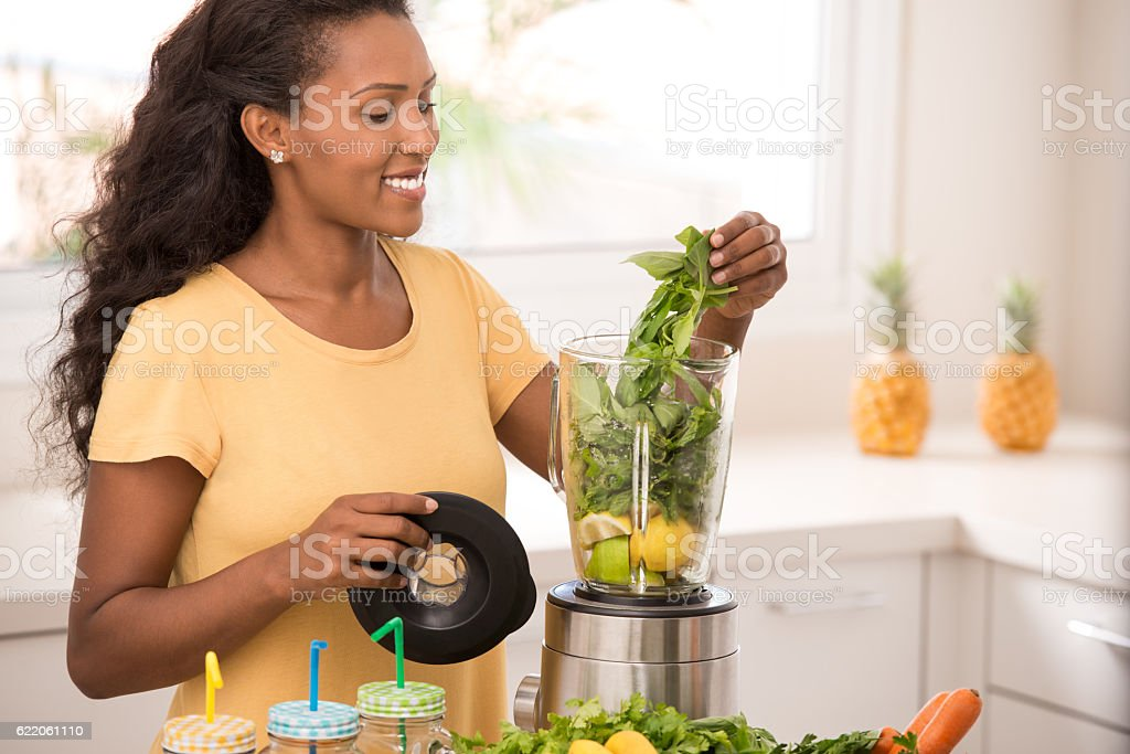 Woman preparing lemonade at kithcen. stock photo