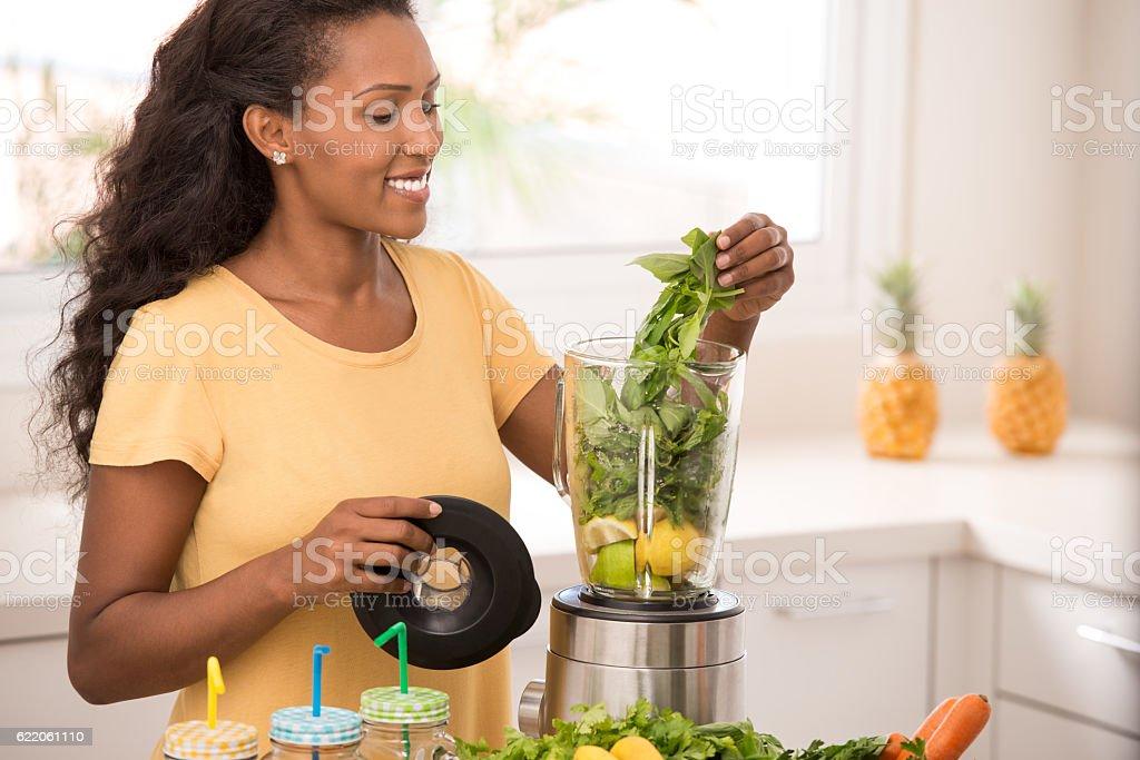 Woman preparing lemonade at kithcen. stock photo