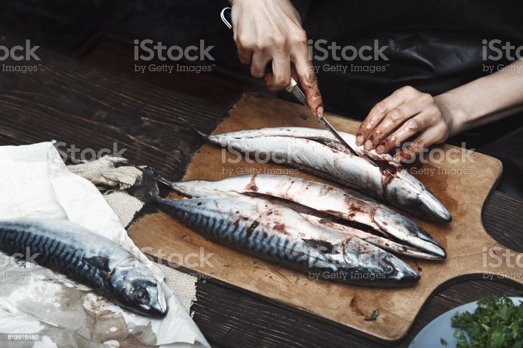 Woman preparing mackerel fish stock photo