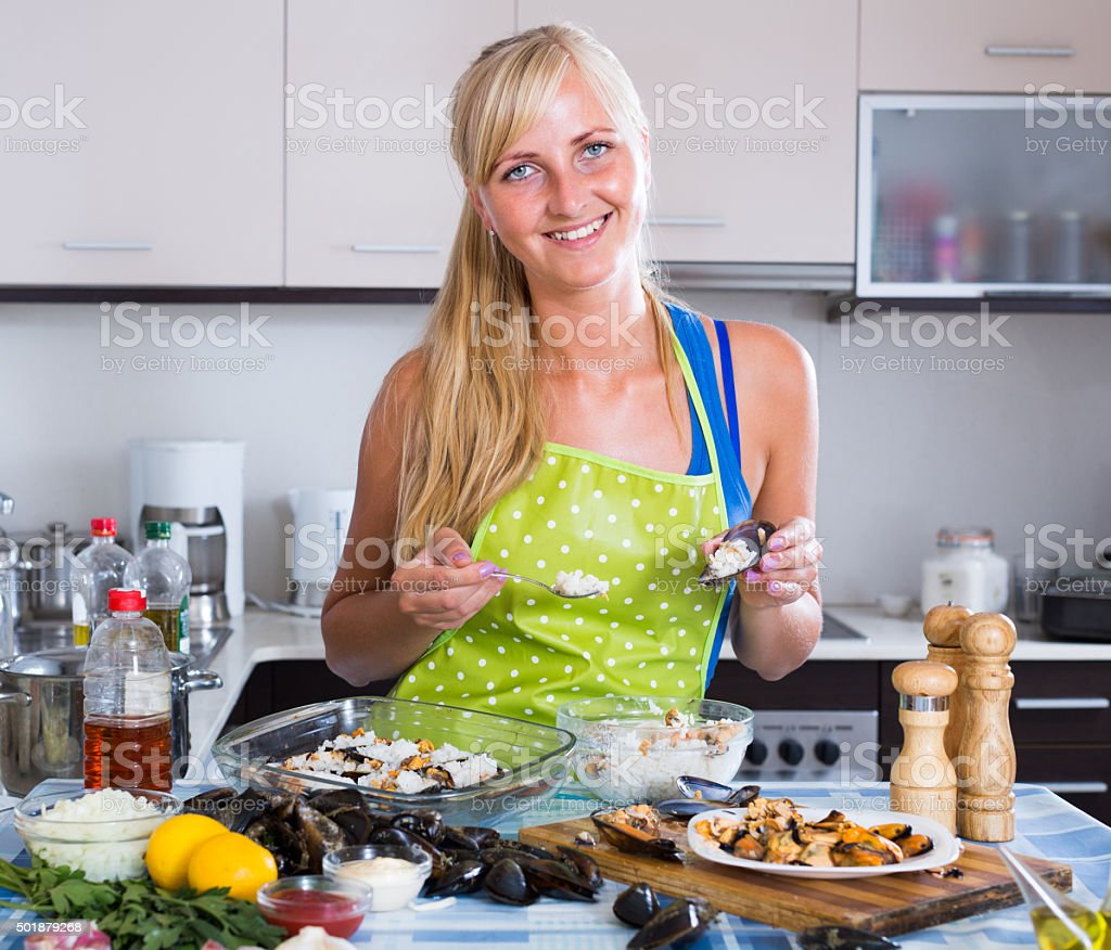 woman preparing mussels with rice stock photo