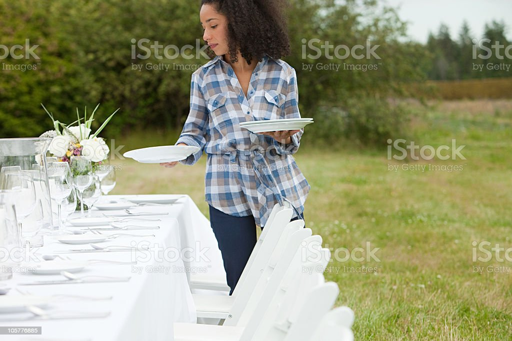 Woman preparing table for dinner party in a field stock photo