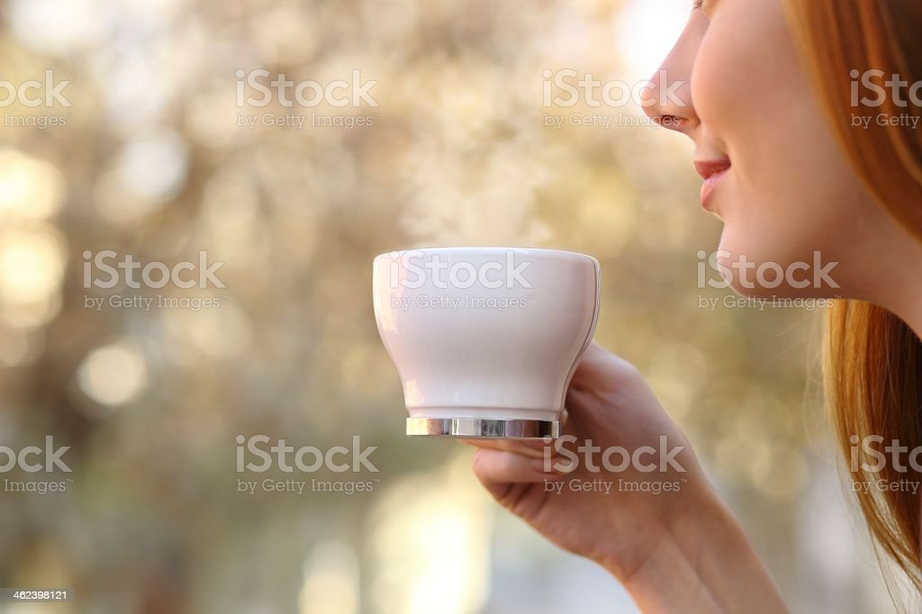 A woman preparing to drink her tea stock photo