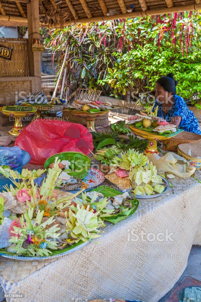UBUD, INDONESIA - AUGUST 29, 2008: Woman preparing traditional sacred fruits for ritual stock photo