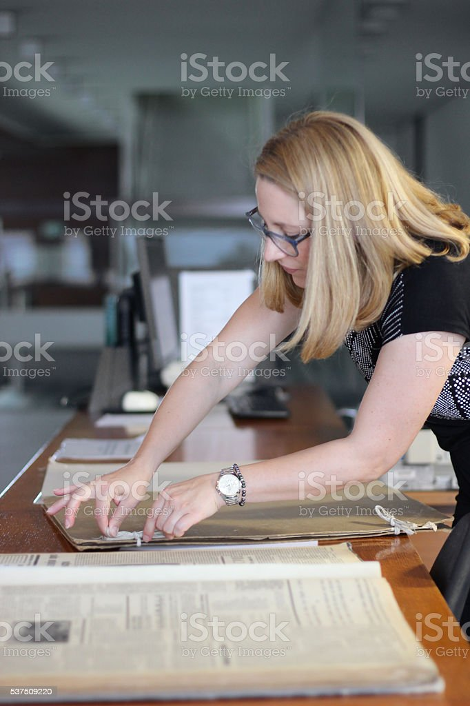 Woman preparing very large newspapers stock photo