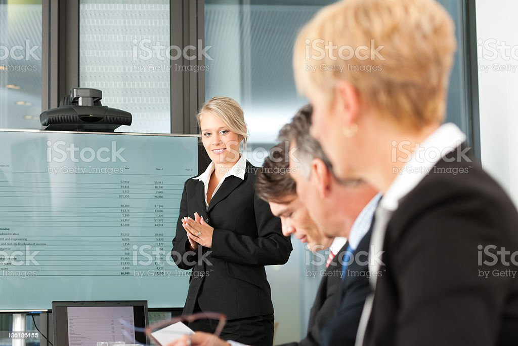 A woman presenting a business idea to her team royalty-free stock photo