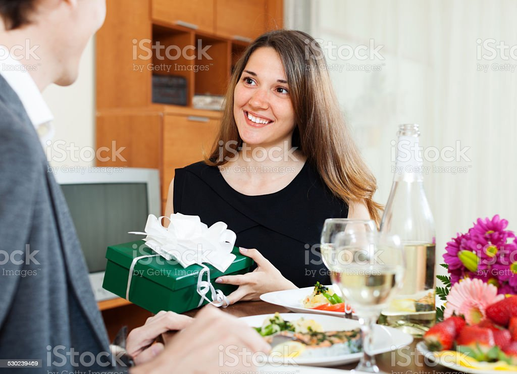 Woman presenting gift to man at table stock photo