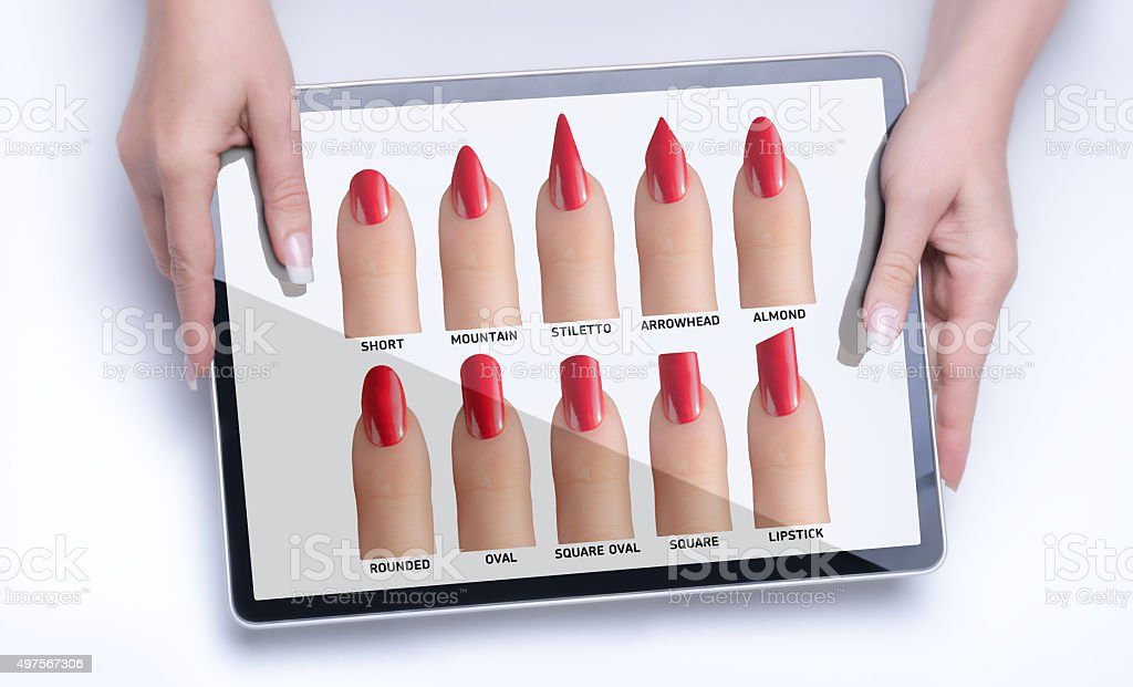 woman presents fingers with different nail shapes on  large tablet stock photo
