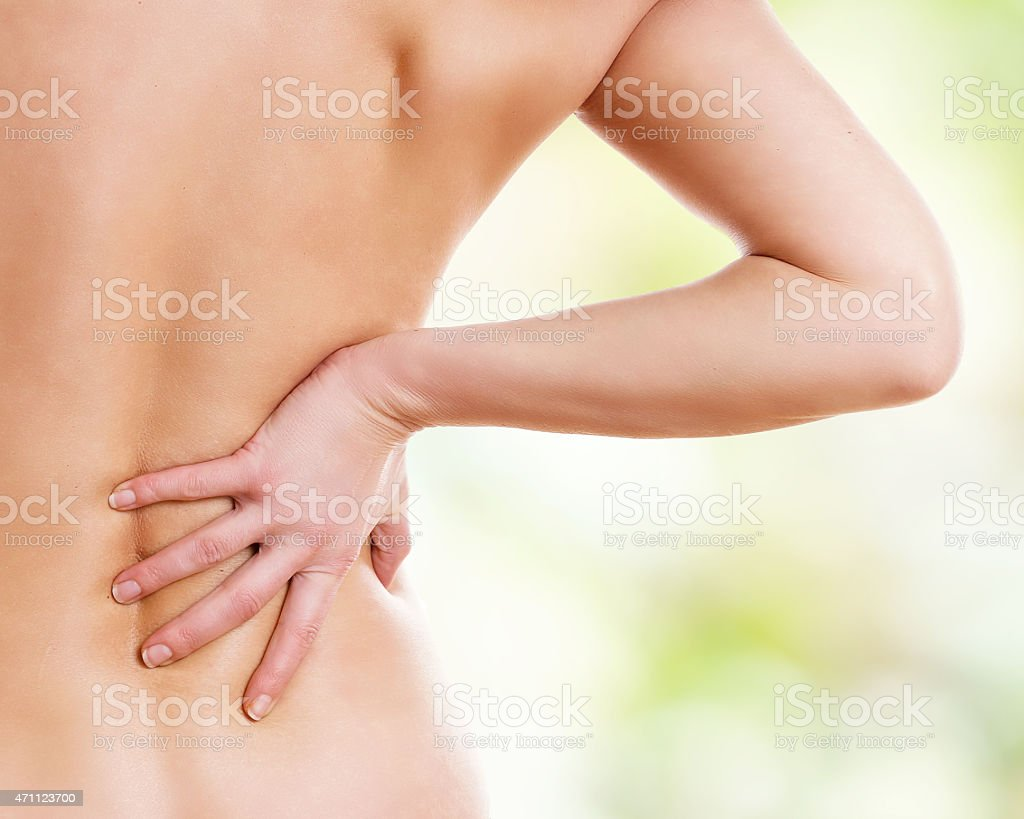 A woman pressing her back due to pain  stock photo