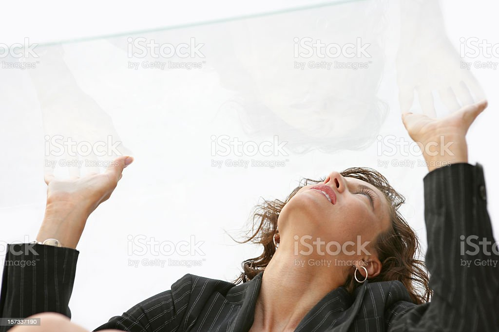 Woman pressing her hands against a glass ceiling stock photo