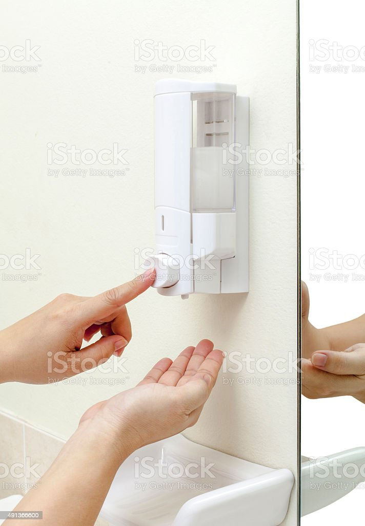 woman pressing the hand gel to her hand stock photo
