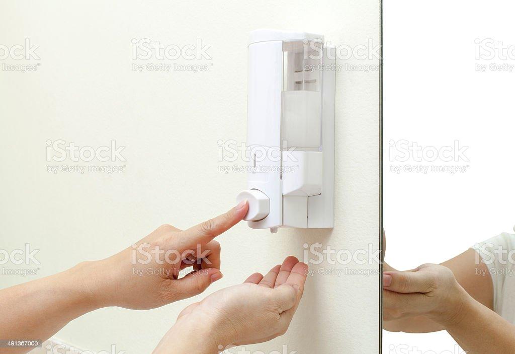 woman pressing the liquid soap stock photo