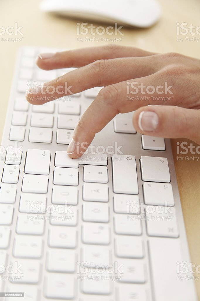 woman Pressing the return button on a white keyboard stock photo